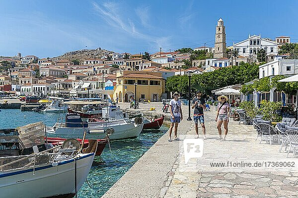 Three tourists  fishing boats in the harbour of Halki with turquoise blue water  promenade with colourful houses of the village of Halki  Halki  Dodecanese  Greece  Europe