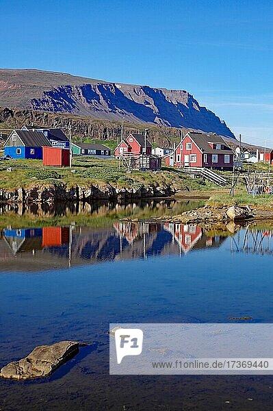 Holzhäuser spiegeln sich im Wasser vor Gebirge  Qeqertarsuaq  Diskoinsel  Artkis  Grönland  Dänemark  Nordamerika Holzhäuser spiegeln sich im Wasser vor Gebirge, Qeqertarsuaq, Diskoinsel, Artkis, Grönland, Dänemark, Nordamerika
