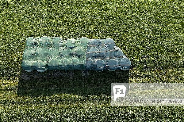 Drohnenaufnahme  In Plastik eingewickelte Strohballen liegen in der Wiese  Agrarlandschaft  Mondseeland  Salzkammergut  Oberösterreich  Österreich  Europa Drohnenaufnahme, In Plastik eingewickelte Strohballen liegen in der Wiese, Agrarlandschaft, Mondseeland, Salzkammergut, Oberösterreich, Österreich, Europa