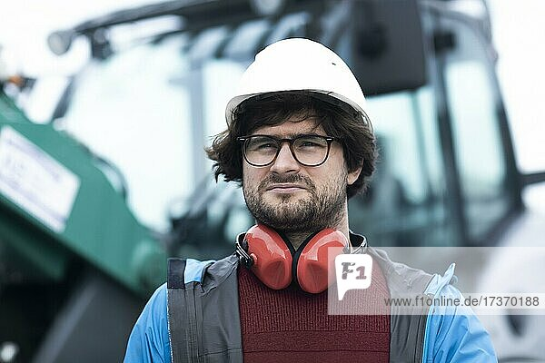 Young engineer with helmet and hearing protection checks outside work with laptop  Freiburg  Baden-Württemberg  Germany  Europe Young engineer with helmet and hearing protection checks outside work with laptop, Freiburg, Baden-Württemberg, Germany, Europe