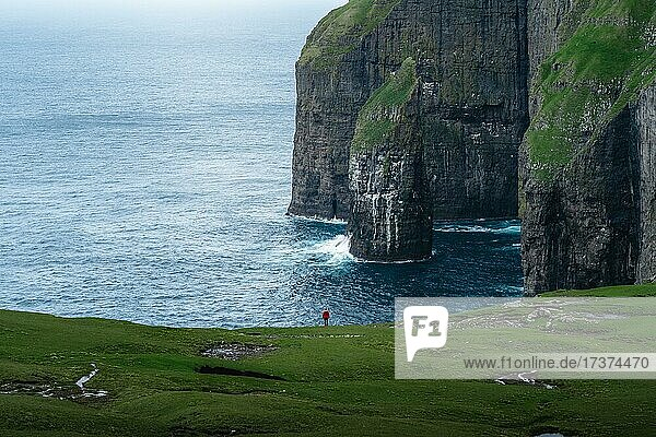 A person standing in the distance in front of Ásmundarstakkur cliff  Sandvik  Suduroy  Faroe Islands  Europe