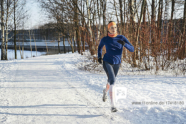 Woman running on snow during sunny day
