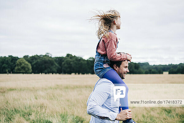 Happy father carrying daughter on shoulders at meadow