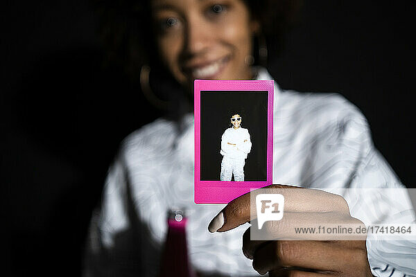 Woman showing polaroid photograph against black background