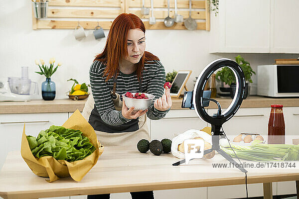 Woman showing strawberry while live streaming through mobile phone in kitchen
