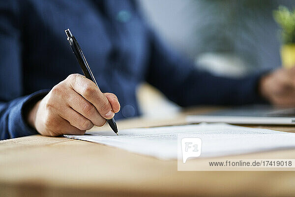 Businessman signing documents while working from home
