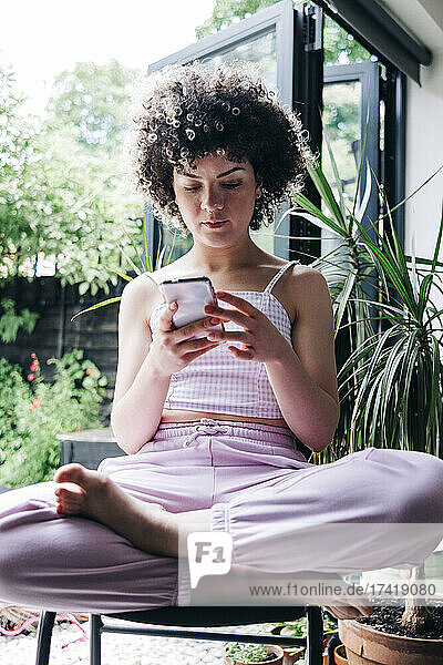 Young woman using mobile phone while sitting cross-legged on chair