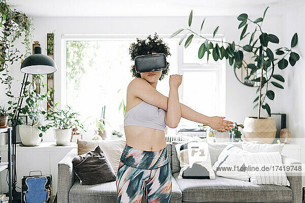 Young woman with virtual reality headset stretching at home