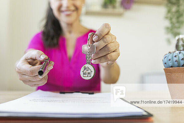 Female freelancer giving pen and house key during real estate agreement at home office