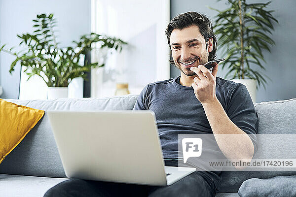 Smiling man sending voicemail while using laptop at home