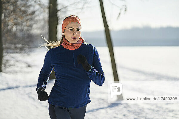 Young woman in sports clothing jogging during winter