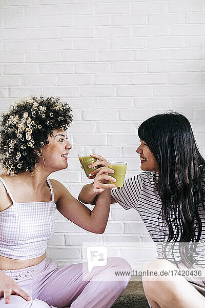 Cheerful female friends drinking smoothie together in front of white brick wall