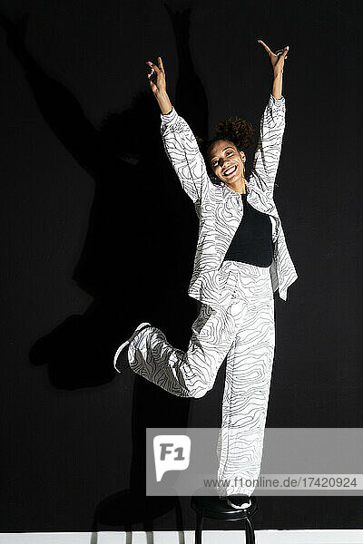 Cheerful woman with arms raised standing on stool against black background