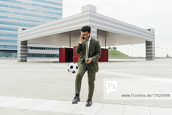 Young businessman talking on mobile phone while playing with soccer ball