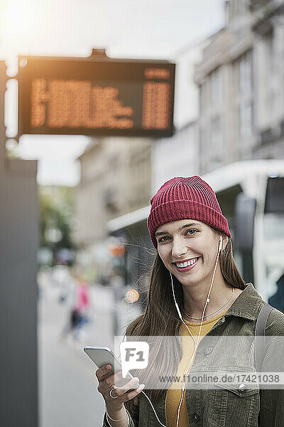 Smiling beautiful woman holding smart phone while listening music