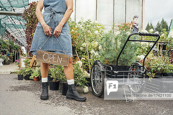 Female greenhouse worker holding open sign while standing by plants in greenhouse