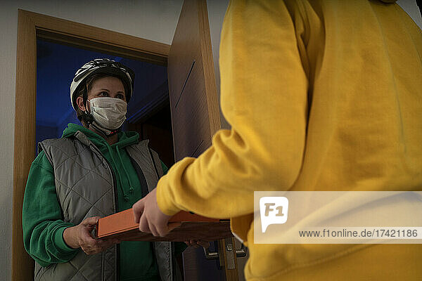Delivery woman giving pizza to boy while standing at doorway during pandemic