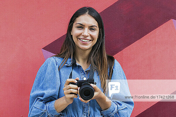 Smiling female freelance worker with camera standing in front of wall