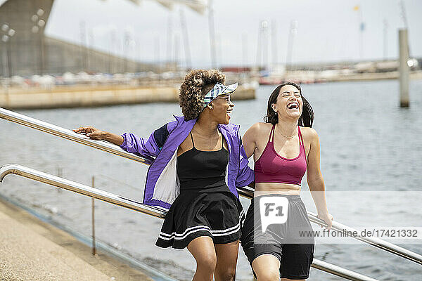 Multi-ethnic female friends laughing while standing together
