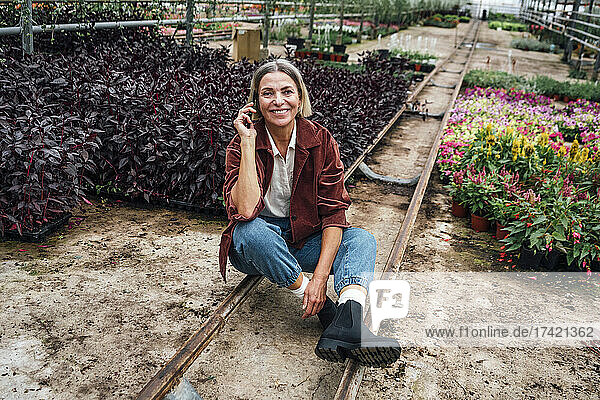 Smiling female farmer talking on mobile phone while sitting in plant nursery