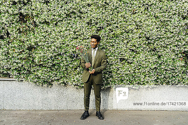 Smiling businessman looking at flower while standing in front of plants on footpath