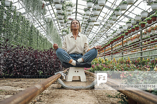 Female farmer meditating while sitting on stool in greenhouse