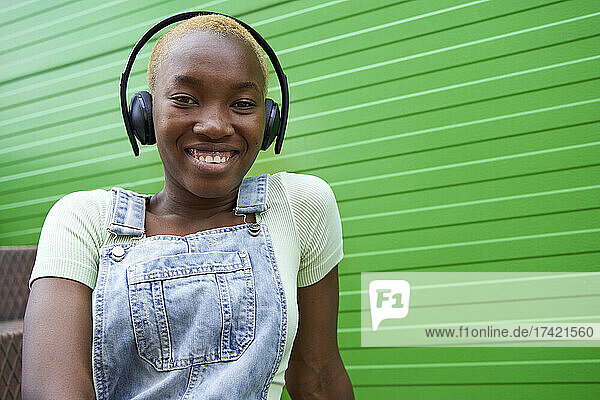 Happy woman with short blond hair listening music through wireless headphones by green wall