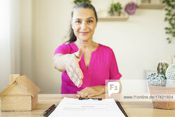 Female real estate agent offering handshake at home office