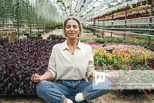 Female farmer practicing yoga while sitting cross-legged in greenhouse