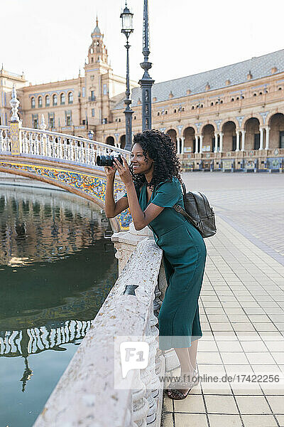 Smiling young woman photographing through camera while leaning on railing at Plaza De Espana  Seville  Spain