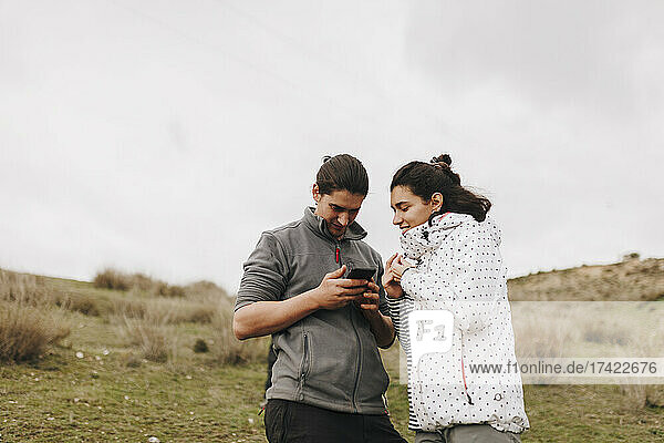 Young man sharing smart phone with female friend in field