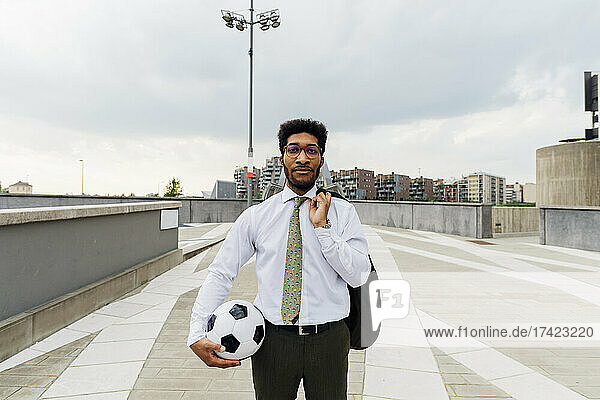 Businessman holding sports ball and blazer while standing on footpath