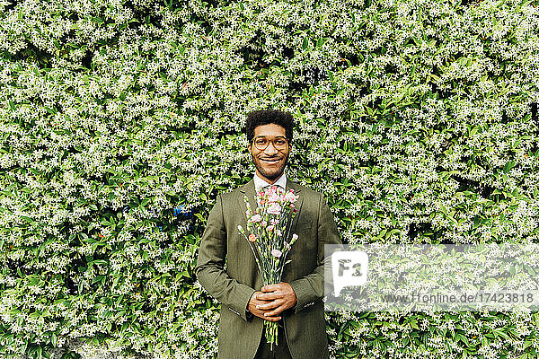 Happy businessman holding bouquet while standing in front of flowering plant