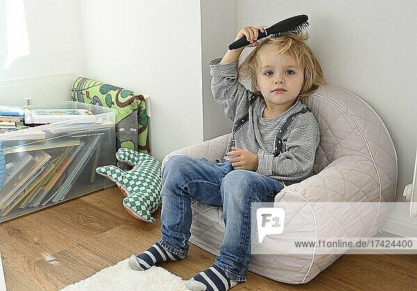 Little blond boy  4 years  brushing his hair  children's room  Baden-Württemberg  Germany  Europe