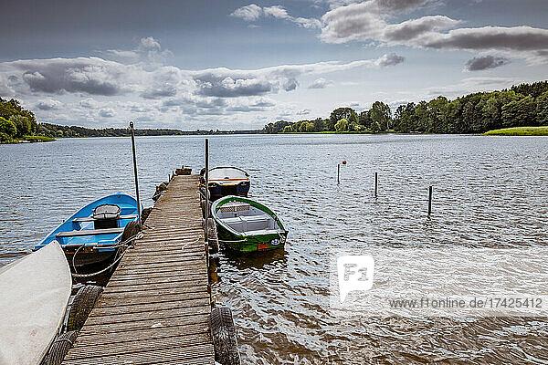 Alte Boote liegen vertäut an einem hölzernen Steg am Nordufer des Brahmsee bei Langwedel