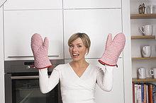junge blonde Hausfrau stehen in Küche zeigen Oven Wanten
