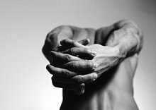 Nackter Mann, der die Arme hinter dem Rücken streckt, die Hände im Vordergrund zusammengehalten, schwarz-weiß.