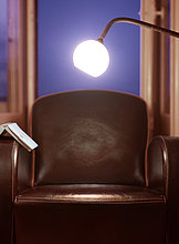 Lichtdurchfluteter Stuhl mit offenem Buch am Arm