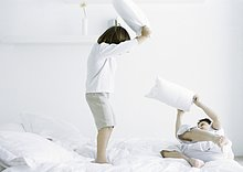 Junge mit Kissen kämpfen auf dem Bett