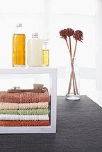 Stilleben Handtücher im Regal kosmetischen Flaschen und Blumen in der vase