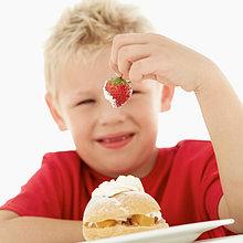 Junge (6-7) eine Erdbeere in seiner Hand haltend