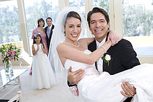 Groom Buchwert Braut in Arme an Hochzeit, Brautjungfer (8-10) und älteres Paar suchen auf, Lächeln, konzentrieren sich auf Vordergrund, Portrait