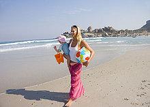Mutter am Strand mit Tochter (12-15 Monate), lächelnd