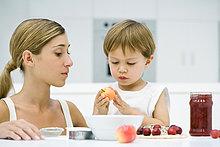 Mutter und Sohn kochen gemeinsam, Junge hält Apfel, beide schauen nach unten