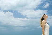 Junge Frau stehend im Freien mit Kopf zurück, Augen geschlossen, Side View, low angle