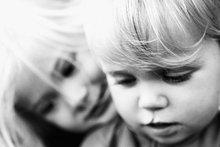 Mädchen stützte sich ihren Kopf auf jüngeren Bruders Schulter, sowohl auf der Suche nach unten, Portrait, Nahaufnahme