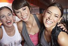 Drei Frauen in Nachtclub, die Spaß und lächelnd