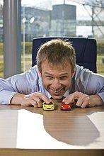Portrait des Kaufmanns spielen mit Spielzeug-Autos