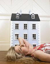 Frau neben einem Puppenhaus
