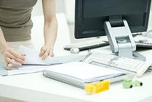 Frau beim Sortieren von Dokumenten auf dem Schreibtisch, Kinderspielzeug im Vordergrund, Ausschnittsansicht